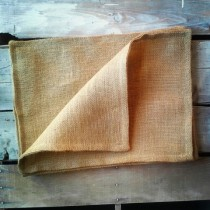 hessian placemat folded on wooden table setting